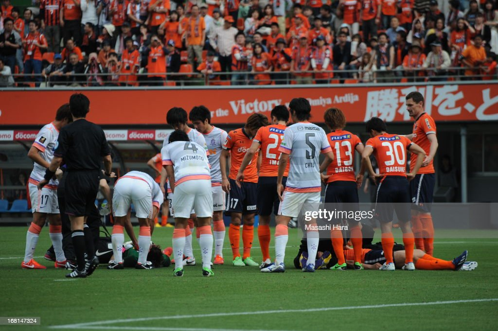 Takamitsu Tomiyama #28 of Omiya Ardija (R) and Takuya Masuda #13 of Sanfrecce Hiroshima (L) lie on the ground after colliding during the J.League match between Omiya Ardija and Sanfrecce Hiroshima at Nack 5 Stadium Omiya on May 6, 2013 in Saitama, Japan.