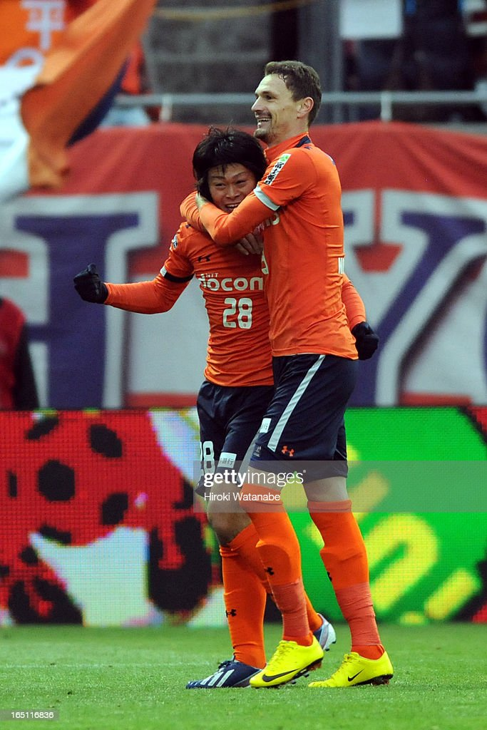 Takamitsu Tomiyama of Omiya Ardija celebrates scoring the third goal with his team mate <a gi-track='captionPersonalityLinkClicked' href=/galleries/search?phrase=Milivoje+Novakovic&family=editorial&specificpeople=880645 ng-click='$event.stopPropagation()'>Milivoje Novakovic</a> during the J.League match between Omiya Ardija and Kashiwa Reysol at Nack 5 Stadium Omiya on March 30, 2013 in Saitama, Japan.