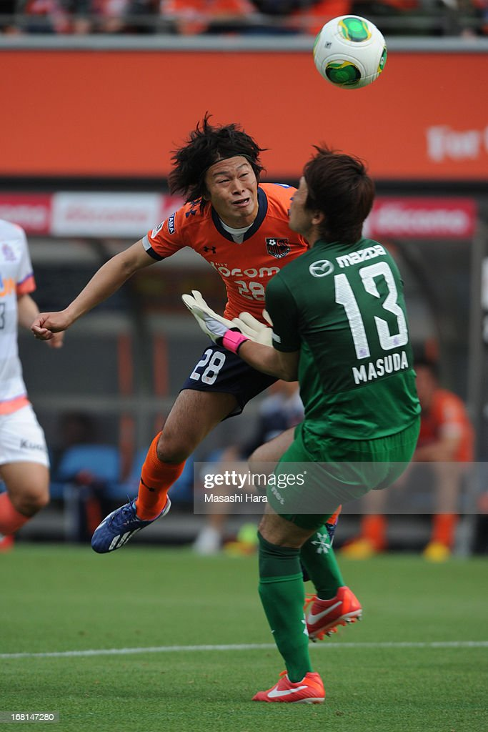 Takamitsu Tomiyama #28 of Omiya Ardija (L) collides with goalkeeper Takuya Masuda #13 of Sanfrecce Hiroshima whilst scoring the second goal during the J.League match between Omiya Ardija and Sanfrecce Hiroshima at Nack 5 Stadium Omiya on May 6, 2013 in Saitama, Japan.