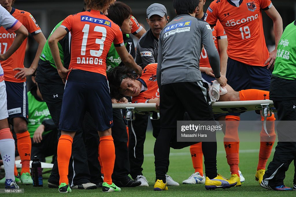 Takamitsu Tomiyama #28 of Omiya Ardija is carried off the pitch on a stretcher after colliding with goalkeeper Takuya Masuda #13 of Sanfrecce Hiroshima whilst scoring the second goal during the J.League match between Omiya Ardija and Sanfrecce Hiroshima at Nack 5 Stadium Omiya on May 6, 2013 in Saitama, Japan.