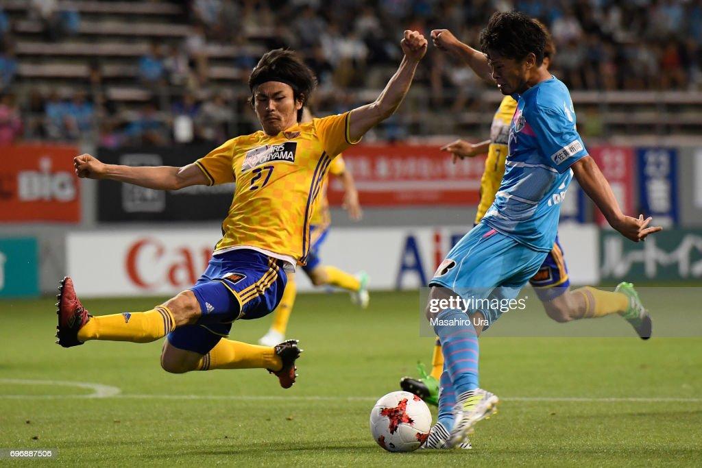 Takamitsu Tomiyama of Sagan Tosu shoots at goal while Kazuki Oiwa of Vegalta Sendai tries to block it during the J.League J1 match between Sagan Tosu and Vegalta Sendai at Best Amenity Stadium on June 17, 2017 in Tosu, Saga, Japan.