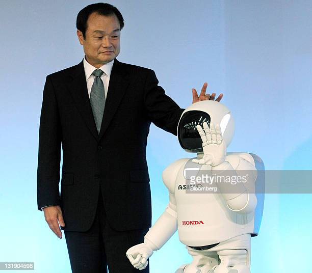 Takanobu Ito president and chief executive officer of Honda Motor Co poses with the company's new ASIMO robot during a news conference in Wako City...
