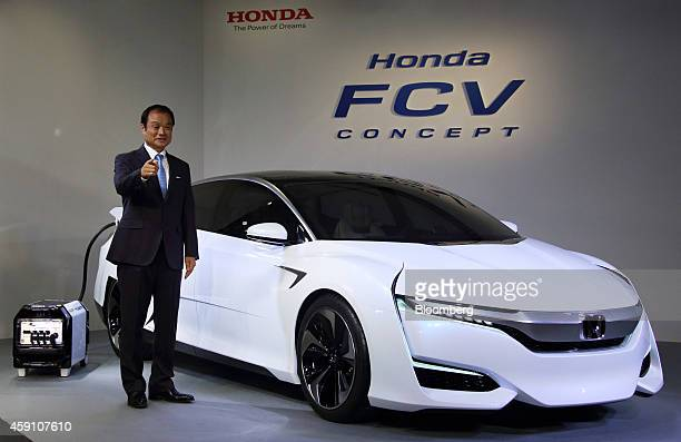 Takanobu Ito president and chief executive officer of Honda Motor Co poses next to the company's Honda FCV Concept hydrogenfueled vehicle during its...