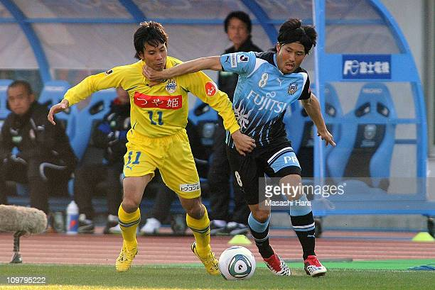 Takanobu Komiyama of Kawasaki Frontale and Tomotaka Kitamura of Montedio Yamagta compete for the ball during a JLeague match at Todoroki Stadium on...