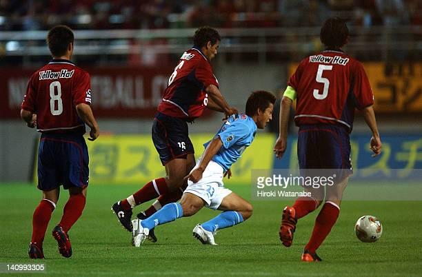 Takashi Fukunishi of Jubilo Iwata is tackled by Fernando Almeida de Oliveira of Kashima Antlers during the JLeague match between Kashima Antlers and...