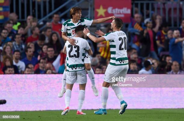 Takashi Inui of Eibar celebrates with team mates after scoring his sides second goal during the La Liga match between Barcelona and Eibar at Camp Nou...