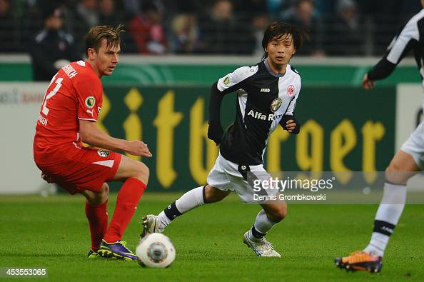 Takashi Inui of Eintracht Frankfurt passes the ball under the pressure of Timo Achenbach of SV Sandhausen during the DFB Cup match between Eintracht...