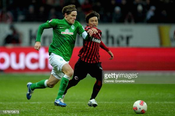 Takashi Inui of Frankfurt challenges Clemens Fritz of Bremen during the Bundesliga match between Eintracht Frankfurt and SV Werder Bremen at...