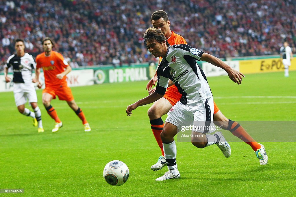 Takashi Inui (front) of Frankfurt is challenged by Marcel Maltritz of Bochum during the DFB Cup second round match between Eintracht Frankfurt and VfL Bochum at Commerzbank-Arena on September 25, 2013 in Frankfurt am Main, Germany.