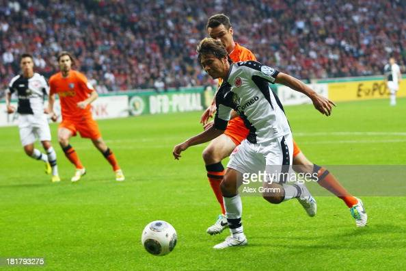 Takashi Inui of Frankfurt is challenged by Marcel Maltritz of Bochum during the DFB Cup second round match between Eintracht Frankfurt and VfL Bochum...