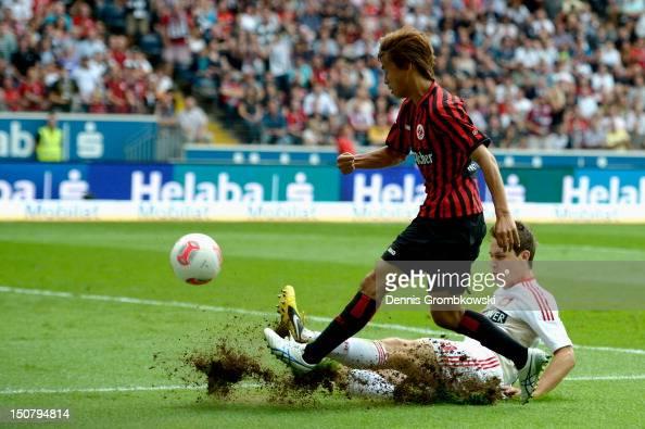Takashi Inui of Frankfurt is challenged by Philipp Wollscheid of Leverkusen during the Bundesliga match between Eintracht Frankfurt and Bayer 04...
