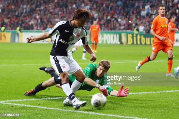 Takashi Inui of Frankfurt scores a disallowed goal against goalkeeper Andreas Luthe of Bochum during the DFB Cup second round match between Eintracht...