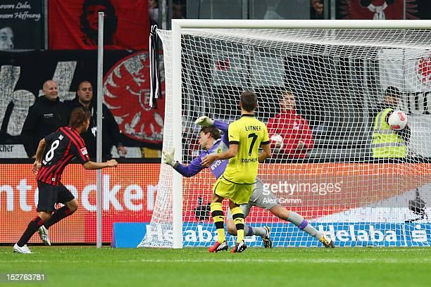 Takashi Inui of Frankfurt scores his team's second goal against goalkeeper Roman Weidenfeller and Moritz Leitner of Dortmund during the Bundesliga...