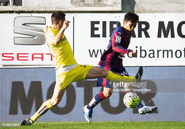 Takashi Inui of SD Eibar duels for the ball with Adrian Lopez of Villarreal CF during the La Liga match between SD Eibar and Villarreal CF at Ipurua...