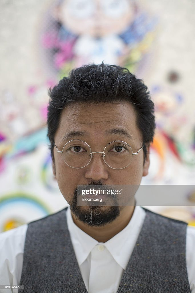Takashi Murakami, a Japanese contemporary artist, poses for a photograph in front of one of his paintings on exhibit at the Galerie Perrotin in Hong Kong, China, on Monday, May 20, 2013. The exhibition 'Takashi Murakami' will be on show until July 6. Photographer: Jerome Favre/Bloomberg via Getty Images