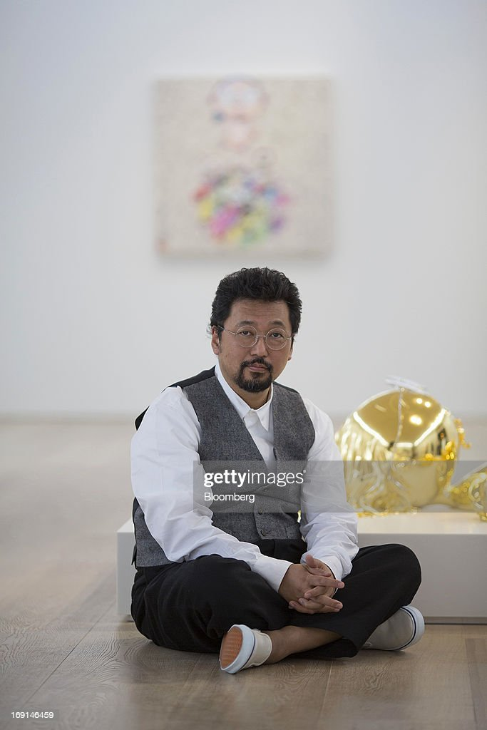 Takashi Murakami, a Japanese contemporary artist, sits for a photograph next to his artwork at the Galerie Perrotin in Hong Kong, China, on Monday, May 20, 2013. The exhibition 'Takashi Murakami' will be on show until July 6. Photographer: Jerome Favre/Bloomberg via Getty Images