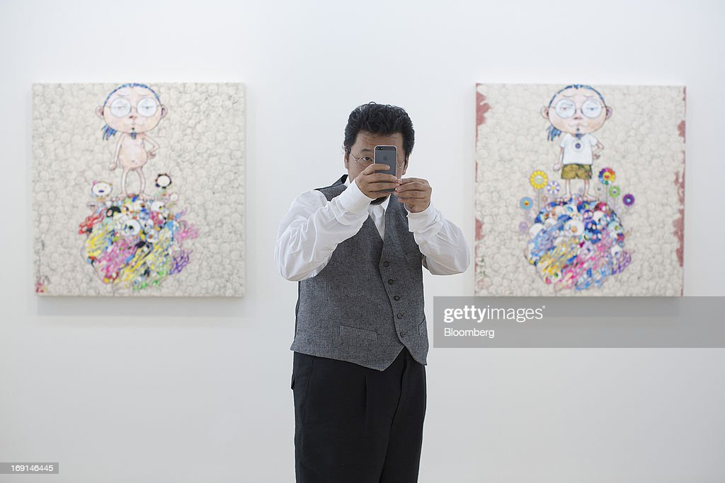 <a gi-track='captionPersonalityLinkClicked' href=/galleries/search?phrase=Takashi+Murakami&family=editorial&specificpeople=588180 ng-click='$event.stopPropagation()'>Takashi Murakami</a>, a Japanese contemporary artist, takes a photograph with a smartphone in front of his paintings on exhibit at the Galerie Perrotin in Hong Kong, China, on Monday, May 20, 2013. The exhibition '<a gi-track='captionPersonalityLinkClicked' href=/galleries/search?phrase=Takashi+Murakami&family=editorial&specificpeople=588180 ng-click='$event.stopPropagation()'>Takashi Murakami</a>' will be on show until July 6. Photographer: Jerome Favre/Bloomberg via Getty Images