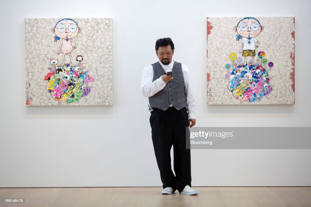 <a gi-track='captionPersonalityLinkClicked' href=/galleries/search?phrase=Takashi+Murakami&family=editorial&specificpeople=588180 ng-click='$event.stopPropagation()'>Takashi Murakami</a>, a Japanese contemporary artist, uses a smartphone in front of his paintings on exhibit at the Galerie Perrotin in Hong Kong, China, on Monday, May 20, 2013. The exhibition '<a gi-track='captionPersonalityLinkClicked' href=/galleries/search?phrase=Takashi+Murakami&family=editorial&specificpeople=588180 ng-click='$event.stopPropagation()'>Takashi Murakami</a>' will be on show until July 6. Photographer: Jerome Favre/Bloomberg via Getty Images