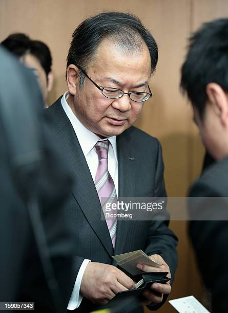 Takashi Okuda president of Sharp Corp exchanges business cards before attending a group interview at the company's headquarters in Osaka Japan on...