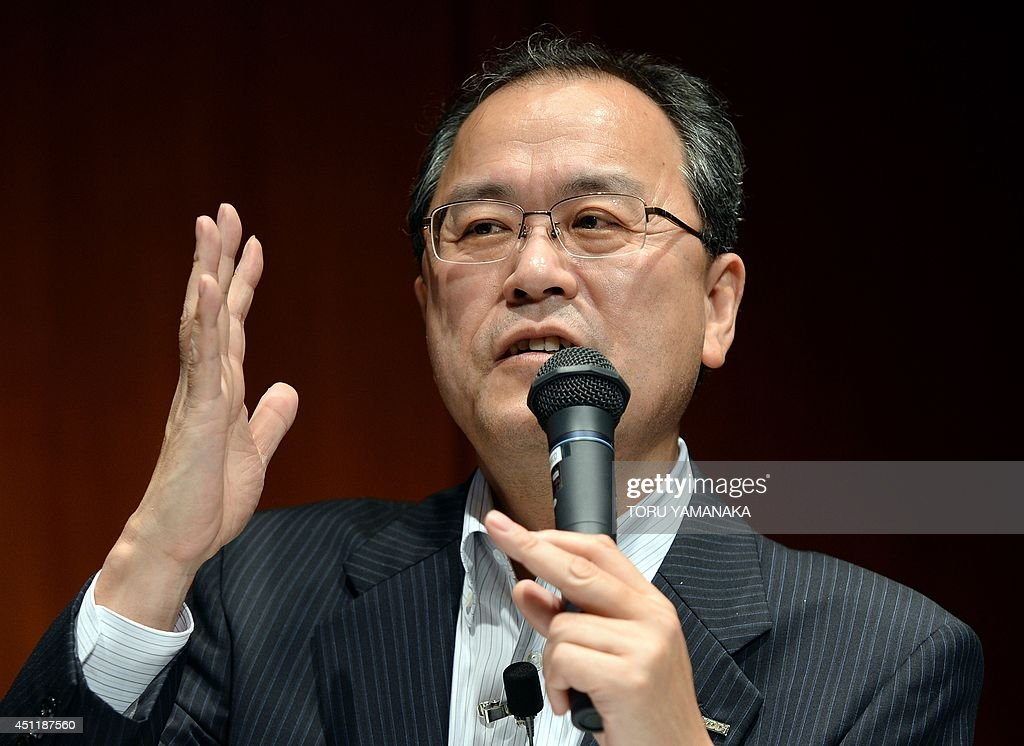Takashi Tanaka president of Japan's telecom company KDDI gestures as he answers questions during a press conference in Tokyo on June 25 2014 KDDI on...