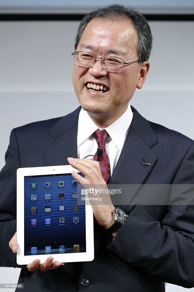 Takashi Tanaka, president of KDDI Corp., holds an Apple Inc. iPad during a launch event at a KDDI store in Tokyo, Japan, on Friday, Nov. 30, 2012. The iPad Mini went on sale at KDDI and Softbank Corp. stores in Japan today. Photographer: Kiyoshi Ota/Bloomberg via Getty Images