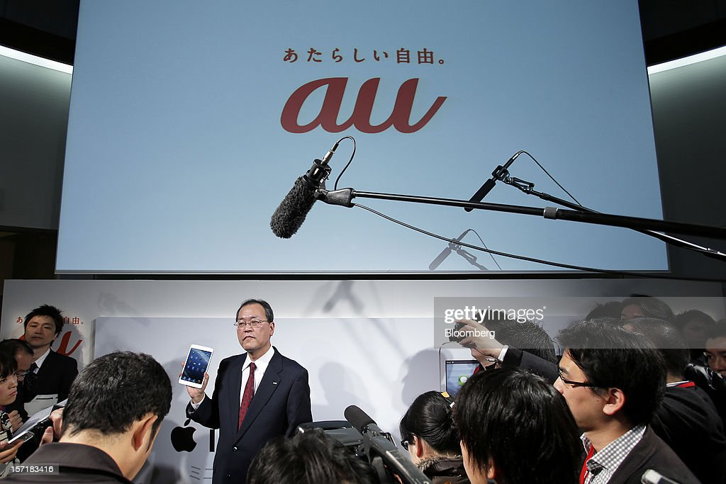 Takashi Tanaka president of KDDI Corp holds an Apple Inc iPad Mini as he speaks to the media after a launch event at a KDDI store in Tokyo Japan on...