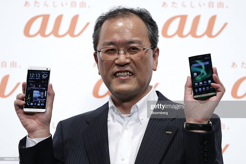 Takashi Tanaka president of KDDI Corp holds the company's au brand smartphones HTC J One HTL22 manufactured by HTC Corp left and Urbano L01...
