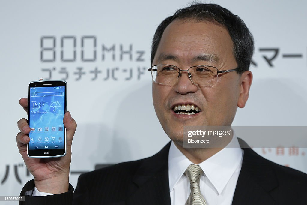 Takashi Tanaka president of KDDI Corp holds the company's 'au' brand smartphone the Isai LGL22 manufactured by LG Electronics Inc during a product...