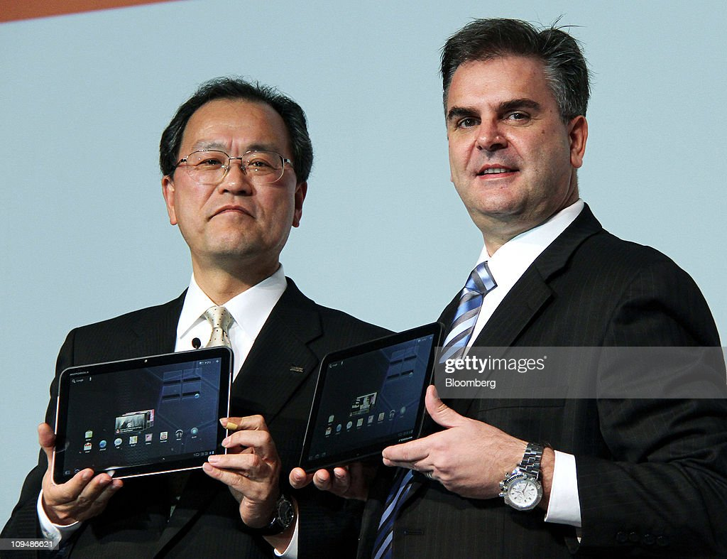 Takashi Tanaka, president of KDDI Corp., left, and Spiros Nikolakopoulos, vice president of Motorola Mobility Inc., hold Motorola XOOM tablet devices manufactured by Motorola Mobility Inc., during an unveiling in Tokyo, Japan, on Monday, Feb. 28, 2011. KDDI is Japan's second-largest mobile-phone operator. Photographer: Haruyoshi Yamaguchi/Bloomberg via Getty Images