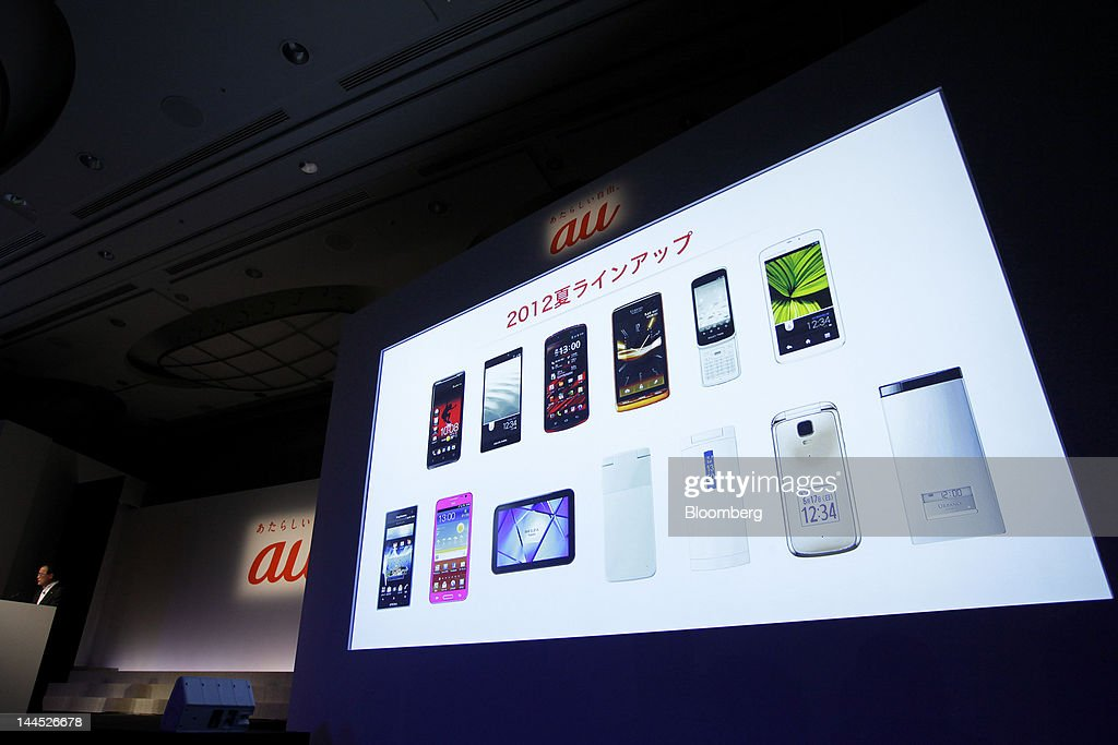 Takashi Tanaka president of KDDI Corp left speaks during the unveiling of the company's new products and services in Tokyo Japan on Tuesday May 15...