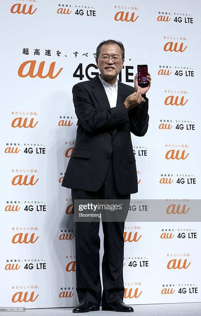 Takashi Tanaka, president of KDDI Corp., poses with the HTC J smartphone during the unveiling of the company's new smartphone line-up in Tokyo, Japan, on Wednesday, Oct. 17, 2012. KDDI is Japan's second-largest mobile-phone carrier. Photographer: Tomohiro Ohsumi/Bloomberg via Getty Images