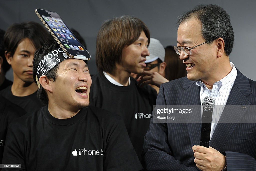 Takashi Tanaka president of KDDI Corp right speaks with a customer during a launch event for the Apple Inc iPhone 5 in Tokyo Japan on Friday...