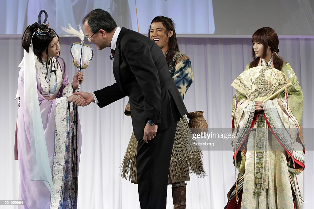 Takashi Tanaka president of KDDI Corp second left shakes hands with model and actress Nanao left while actor Kenta Kiritani second from right and...