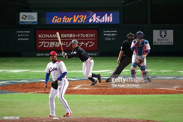 Takashi Toritani of Japan hits a sacrifice fly in the top of ninth inning during the World Baseball Classic First Round Group A game between Japan...