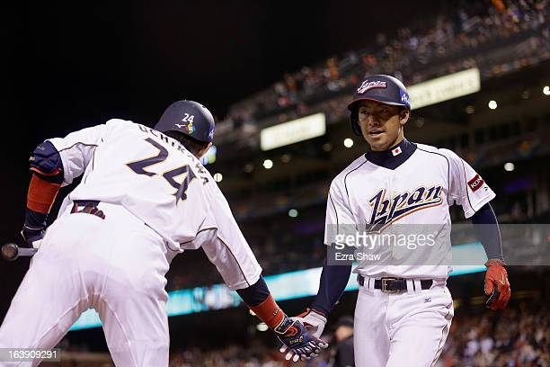 Takashi Toritani of Japan is congratulated by Seiichi Uchikawa after he scored in the eighth inning against Puerto Rico in the semifinals of the...