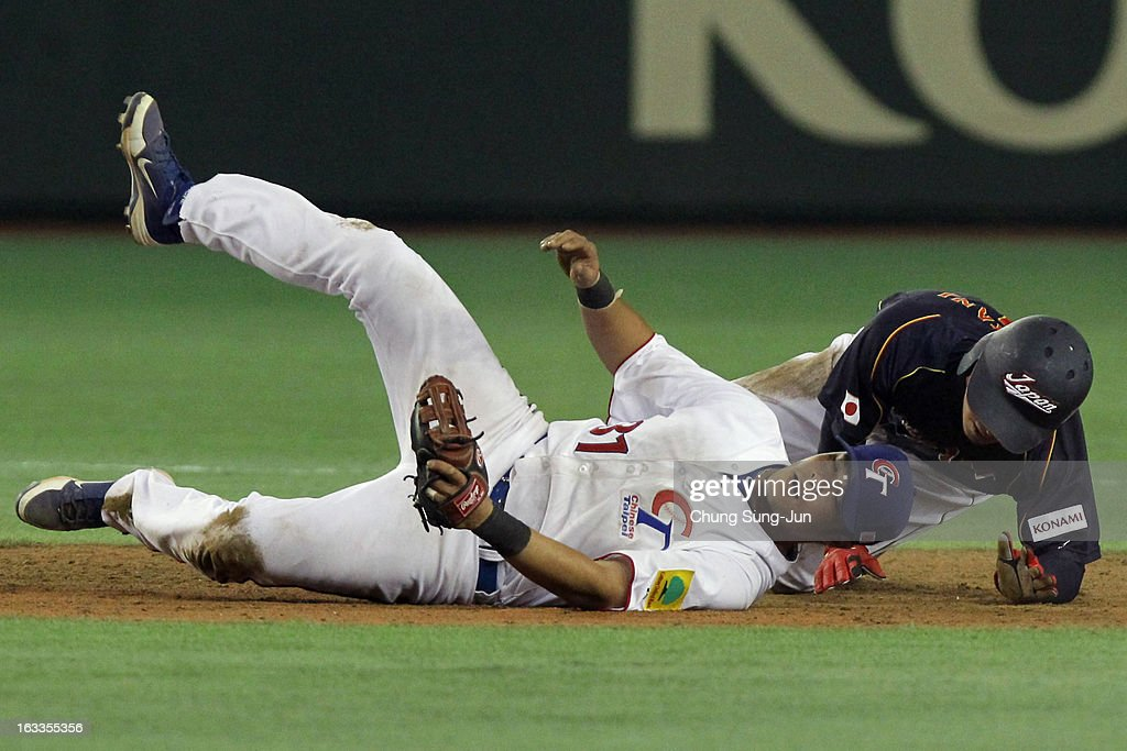 Takashi Toritani # 1 of Japan slides safely into second base as Chih-Sheng Lin # 31 of Chinese Taipei tries to tag him in the ninth inning during the World Baseball Classic Second Round Pool 1 game between Japan and Chinese Taipei at Tokyo Dome on March 8, 2013 in Tokyo, Japan.