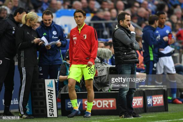 Takashi Usami of Augsburg walks past head coach Manuel Baum during the Bundesliga match between FC Schalke 04 and FC Augsburg at VeltinsArena on...