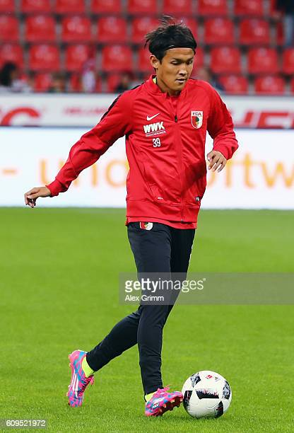 Takashi Usami of Augsburg warms up prior to the Bundesliga match between Bayer 04 Leverkusen and FC Augsburg at BayArena on September 21 2016 in...