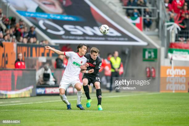 Takashi Usami of FC Augsburg and Lukas Kluenter of Cologne battle for the ball during the Bundesliga match between FC Augsburg and 1 FC Koeln at WWK...