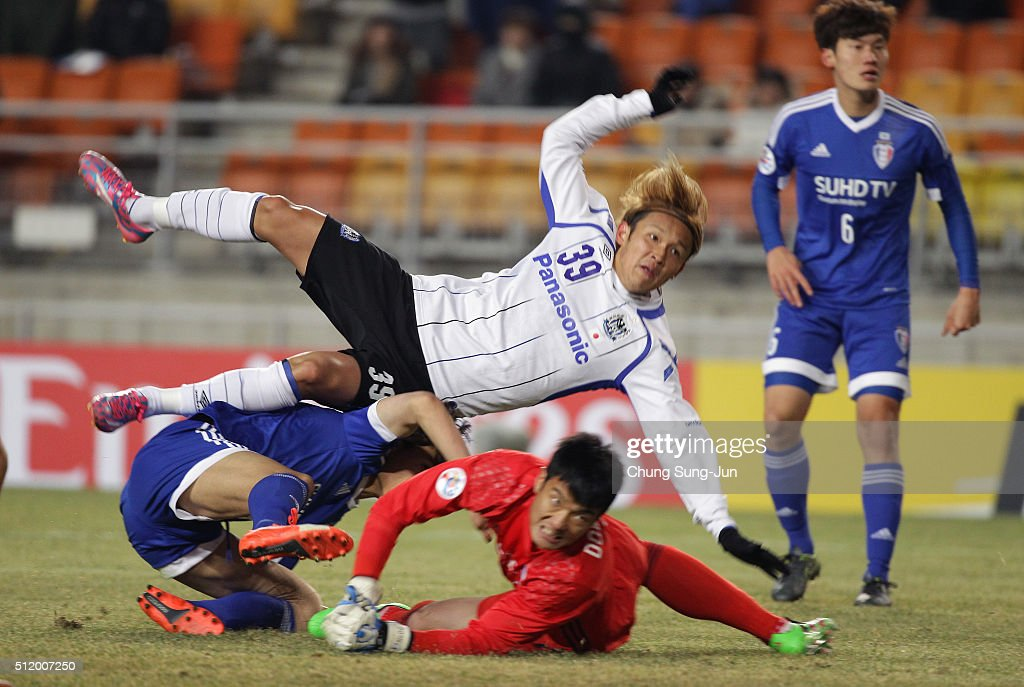 Takashi Usami of Gamba Osaka competes for the ball with No DongGeon and Min SangGi of Suwon Samsung Bluewings during the AFC Champions League Group G...