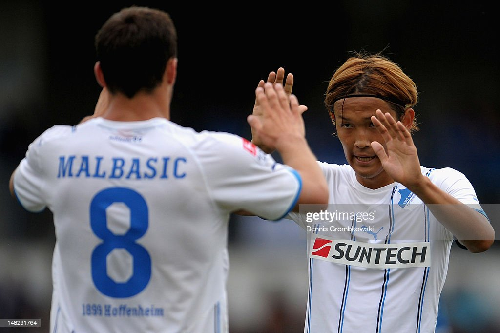 Takashi Usami of Hoffenheim celebrates with teammate Filip Malbasic after scoring his team's third goal during the friendly match between FCAstoria...