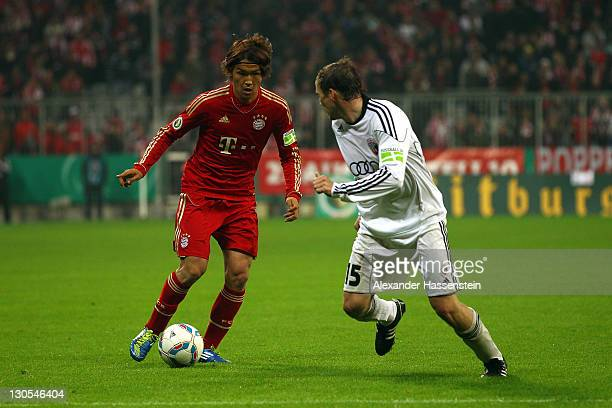 Takashi Usami of Muenchen battles for the ball with Tobias Fink of Ingolstadt during the DFB Cup second round match between FC Bayern Muenchen and FC...