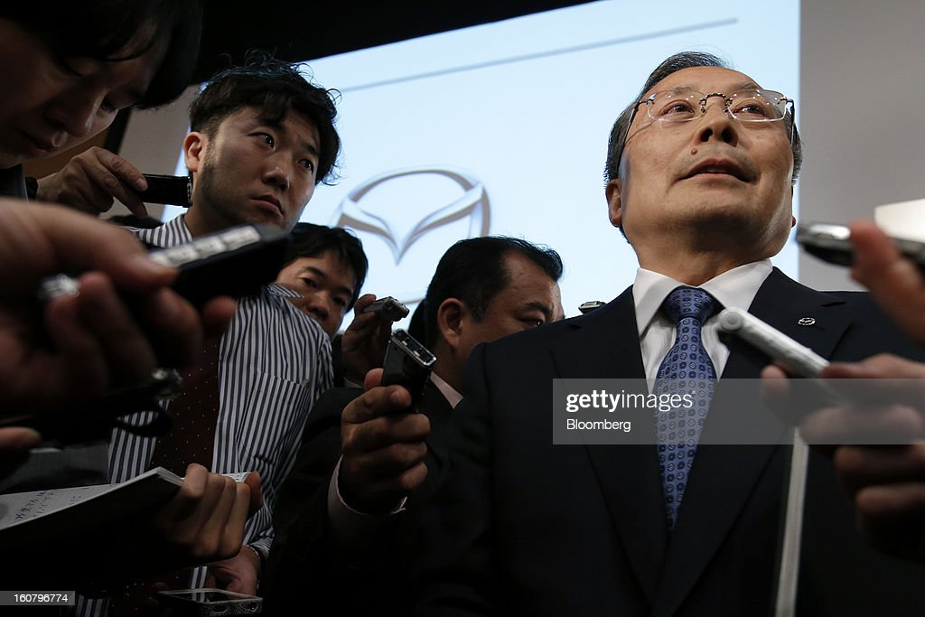 Takashi Yamanouchi, chief executive officer of Mazda Motor Corp., right, speaks to members of the media following a news conference in Tokyo, Japan, on Wednesday, Feb. 6, 2013. Mazda, the best performer on the Nikkei 225 Stock Average in the past three months, more than doubled its full-year profit forecast on a weaker yen and demand for its fuel-efficient vehicles. Photographer: Kiyoshi Ota/Bloomberg via Getty Images