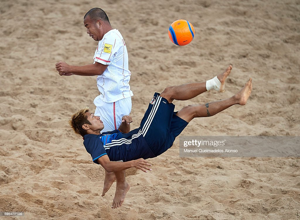 Takasuke Goto (R) of Japan attempts a scissor kick shot on goal in front Le Kim Tuan of Vietnam during the Continental Beach Soccer Tournament match between Japan and Vietnam at Municipal Sports Center on August 25, 2016 in Ordos of Inner Mongolia Autonomous Region, China.