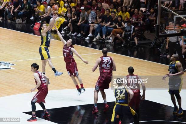 Takatoshi Furukawa of the Tochigi Brex shoots over Naoto Tsuji of the Kawasaki Brave Thunders during the B League final match between Kawasaki Brave...