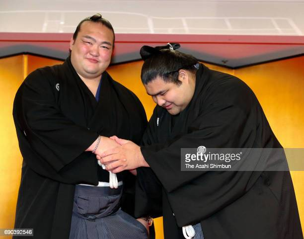 Takayasu shakes hands with yokozuna Kisenosato after his promotion to Ozeki second highest rank in sumo at Tagonoura Stable on May 31 2017 in Tokyo...