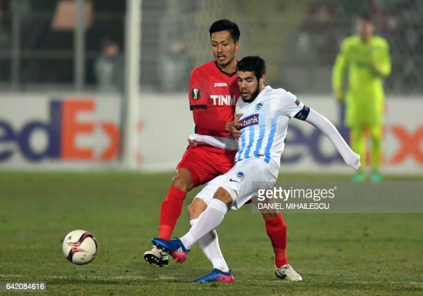 Takayuki Seto of Astra Giurgiu vies for the ball with Alejandro Pozuelo of KRC Genk during the UEFA Europa League round of 32 firstleg football match...