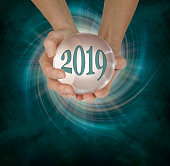 female hands holding a large scrying ball containing the year 2019 against a deep green vortex spiral and copy space  below