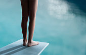 Young boy or girl is standing on a diving board and ready to jump