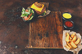 Take away burger menu on wooden tray copy space. Black bun cheeseburger with baked potato wedges and sauces set, fast food concept